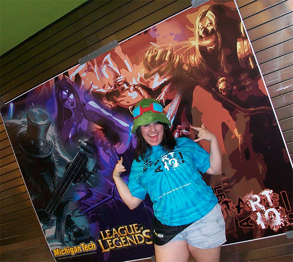 """Picture of Briana in front of a large scale poster of mebmers of the League of Legends band Pentakill in the highly stylized style used for the tournament, with the """"Let's Start a Riot!"""" logo in teh bottom right. Briana is wearing a tye-dyed t-shirt featuring the logo, which were designed for the tournament as well."""