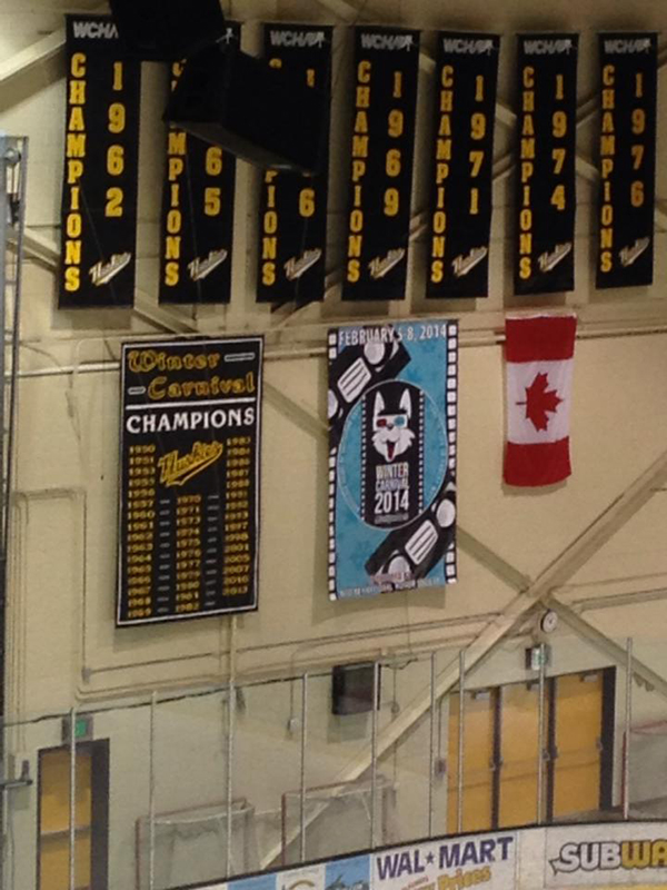 The designed banner for Winter Carnival 2014 displayed in the McInnes Ice Arena at Michigan Tech. It is shown on a wall above the rink, under the champion banners and flanked by the Winter Carnival Champion banner and a Canadian flag.